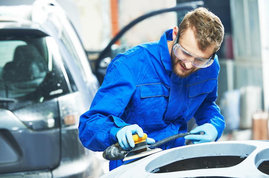 auto mechanic worker  polishing bumper car