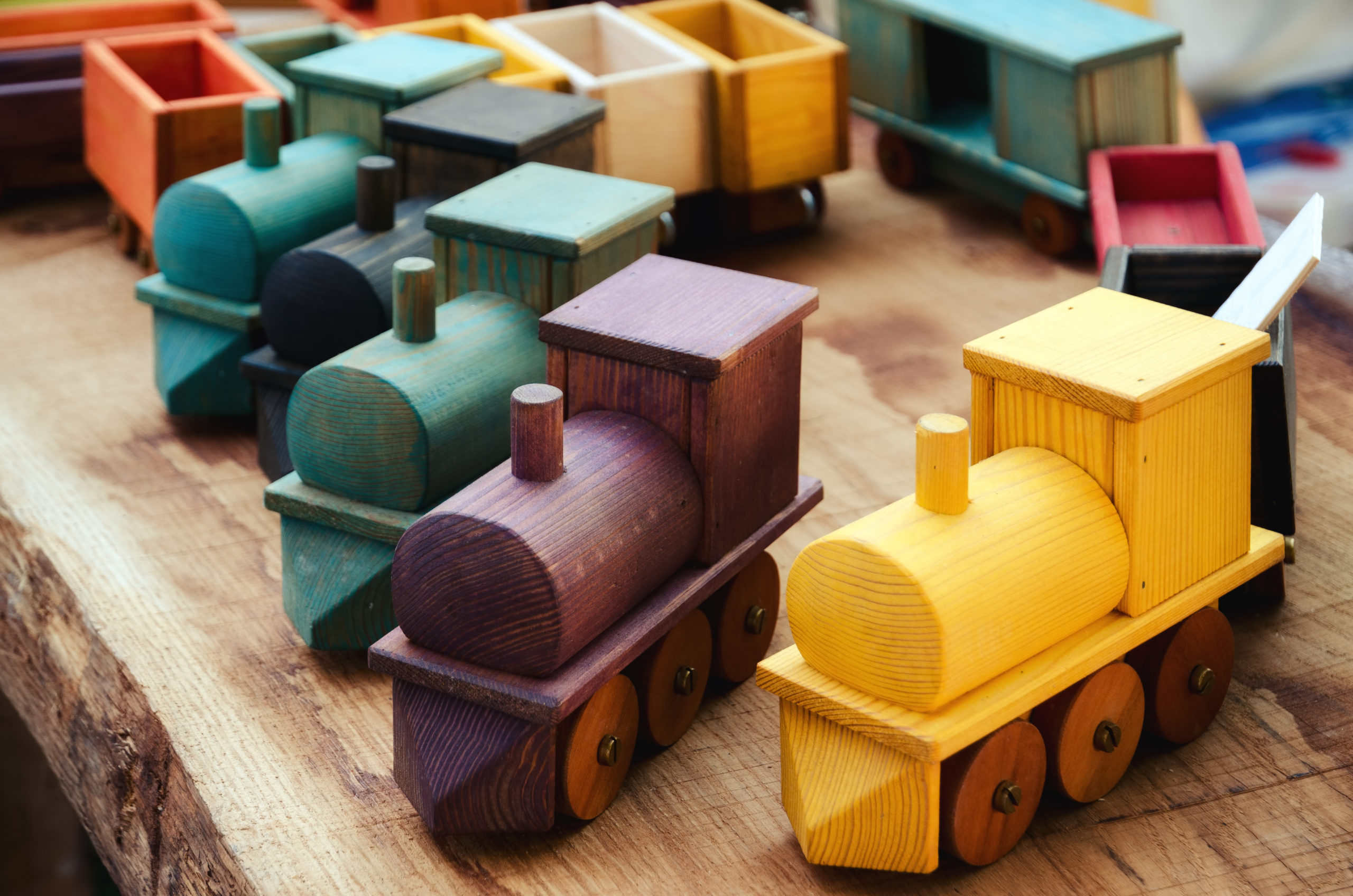 Many wooden train toys on a wood table