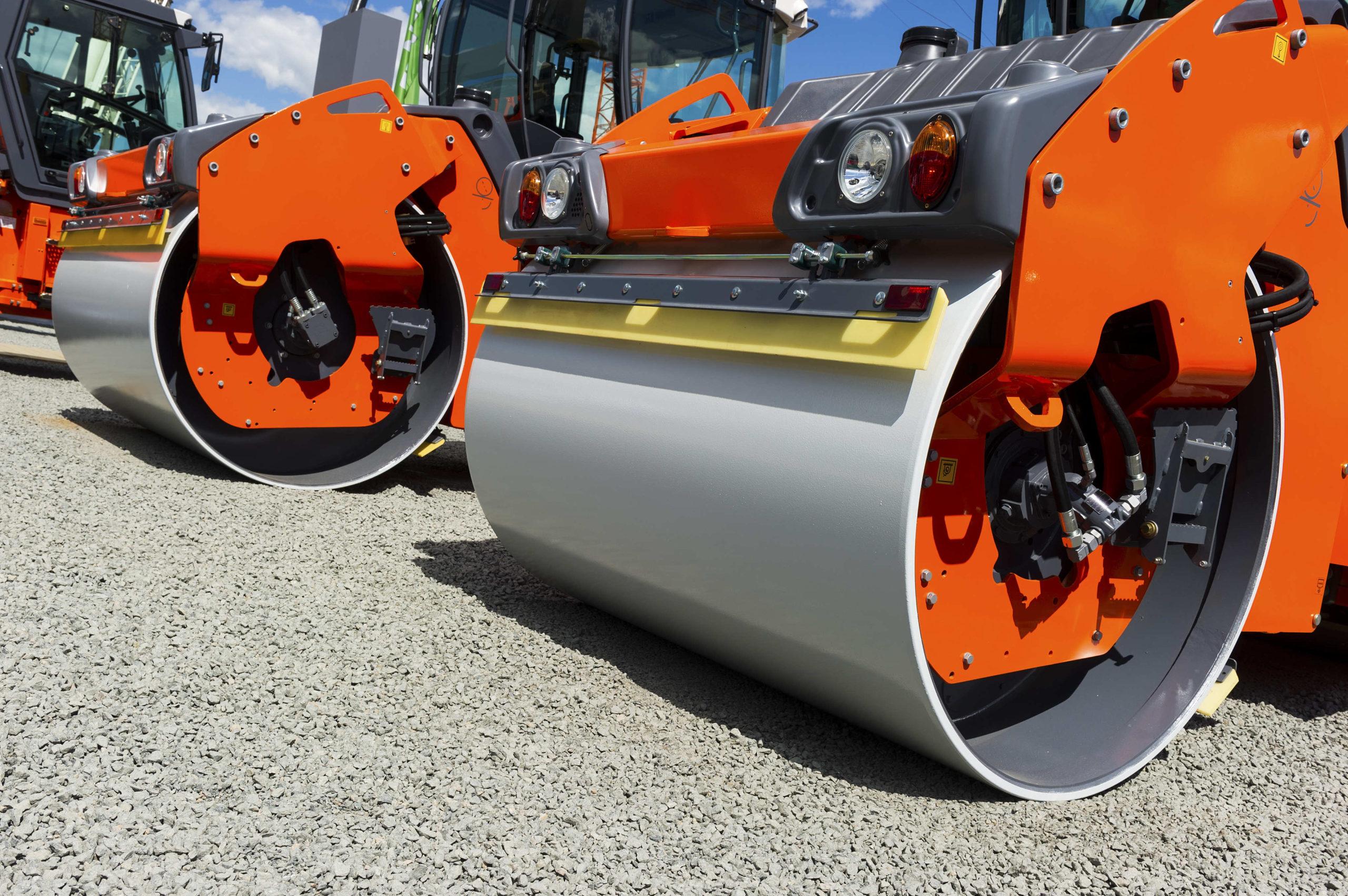 Steamroller, heavy road roller and vibration roller compactor in row on grey gravel, construction industry, blue sky and white clouds on background